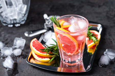 Grapefruit and fresh rosemary gin cocktail with juice, cold summer citrus refreshing drink or beverage with ice