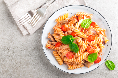 Pasta spirali stirred with fried pieces of chicken, cherry tomatoes and tomato sauce 写真素材 - 95801602