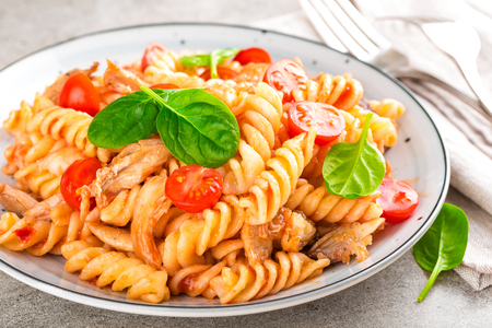 Pasta spirali stirred with fried pieces of chicken, cherry tomatoes and tomato sauce Stock Photo
