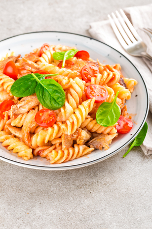 Pasta spirali stirred with fried pieces of chicken, cherry tomatoes and tomato sauce Фото со стока