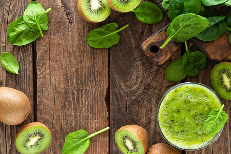 Kiwi smoothie drink of spinach leaves and fresh fruits on wooden rustic table, healthy detox diet