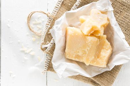 白い木製の背景にパルメザンチーズ 写真素材