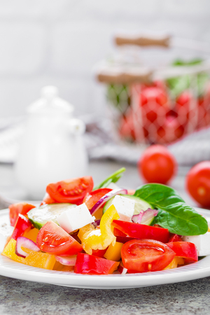 Tomato salad with fresh bell pepper, red onion and feta cheese. Healthy eating Stock Photo