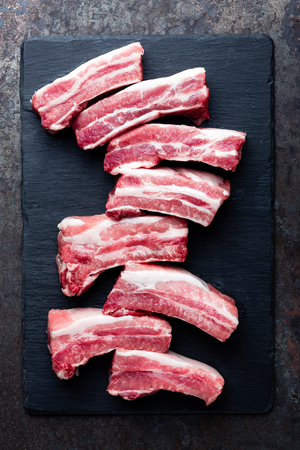 Raw uncooked pork ribs, fresh meat on dark metal background. Top view. Flat lay. Stock Photo