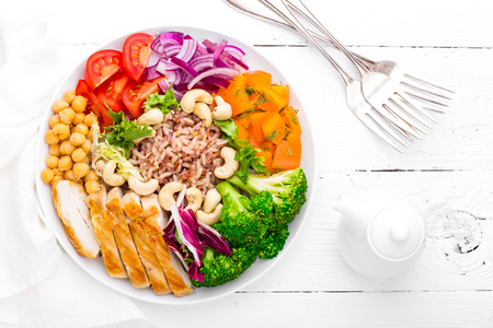Buddha bowl dish with chicken fillet, brown rice, pepper, tomato, broccoli, onion, chickpea, fresh lettuce salad, cashew and walnuts. Healthy balanced eating. Top view. White background