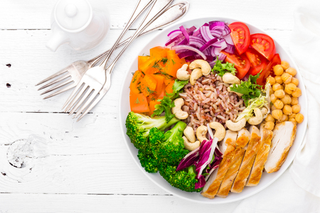 Boeddha schaaltje met kipfilet, bruine rijst, peper, tomaat, broccoli, ui, kikkererwten, verse slasalade, cashewnoten en walnoten. Gezond evenwichtig eten. Bovenaanzicht witte achtergrond Stockfoto - 96797164