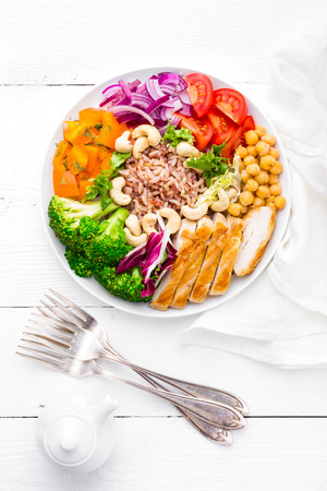 Buddha bowl dish with chicken fillet, brown rice, pepper, tomato, broccoli, onion, chickpea, fresh lettuce salad, cashew and walnuts. Healthy balanced eating. Top view. White background 版權商用圖片 - 96797175