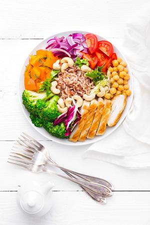 Plato de Buda con filete de pollo, arroz integral, pimiento, tomate, brócoli, cebolla, garbanzos, ensalada de lechuga fresca, anacardos y nueces. Alimentación sana y equilibrada. Vista superior. Fondo blanco Foto de archivo