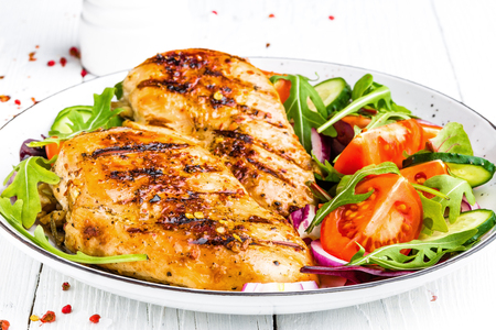 グリルチキン胸肉。フライドチキンフィレとトマト、キュウリ、ルッコラの葉の新鮮な野菜サラダ。チキンミートサラダ。健康的な食べ物。白い背