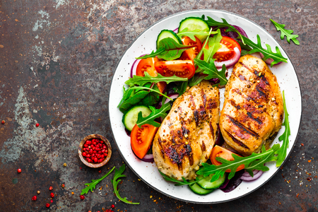 Grilled chicken breast. Fried chicken fillet and fresh vegetable salad of tomatoes, cucumbers and arugula leaves. Chicken meat with salad. Healthy food. Flat lay. Top view. Dark background Imagens
