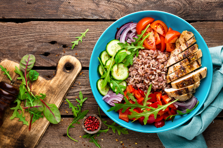 Grilled chicken breast. Fried chicken fillet and fresh vegetable salad of tomatoes, cucumbers, pepper, lettuce and arugula leaves. Chicken meat with salad. Healthy food. Flat lay. Top view. Wooden background