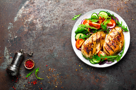 Grilled chicken breast. Fried chicken fillet and fresh vegetable salad of tomatoes, cucumbers and arugula leaves. Chicken meat with salad. Healthy food. Flat lay. Top view. Dark background Standard-Bild
