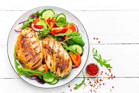 Grilled chicken breast. Fried chicken fillet and fresh vegetable salad of tomatoes, cucumbers and arugula leaves. Chicken meat salad. Healthy food. Flat lay. Top view. White background Stockfoto - 97351490