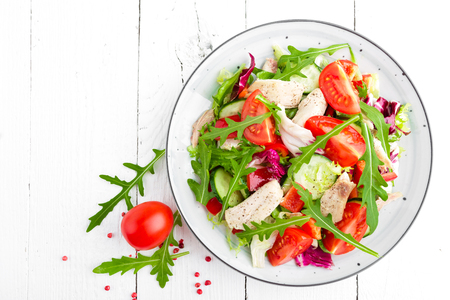 Chicken fillet salad with tomato, lettuce, cucumber and arugula leaves. Fresh vegetable salad with chicken meat. Healthy food. White wooden background. Top view