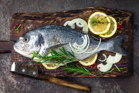 Fresh fish dorado with ingredients for cooking on wooden board. Raw sea bream or dorada fish on dark vintage metal background. Dietary food. Top view Stockfoto
