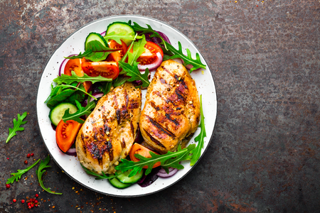 Grilled chicken breast. Fried chicken fillet and fresh vegetable salad of tomatoes, cucumbers and arugula leaves. Chicken meat with salad. Healthy food. Flat lay. Top view. Dark background Foto de archivo