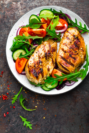Grilled chicken breast. Fried chicken fillet and fresh vegetable salad of tomatoes, cucumbers and arugula leaves. Chicken meat with salad. Healthy food. Flat lay. Top view. Dark background Imagens - 97351828