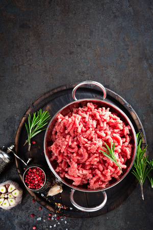 Cooking mince. Raw ground veal meat with ingredients for cooking on black kitchen table. Fresh minced meat, top view Stock Photo