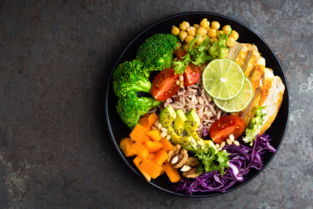 Buddha bowl meal with chicken fillet, brown rice, avocado, pepper, tomato, broccoli, red cabbage, chickpea, fresh lettuce salad, pine nuts and walnuts. Healthy balanced eating. Overhead view Stock fotó