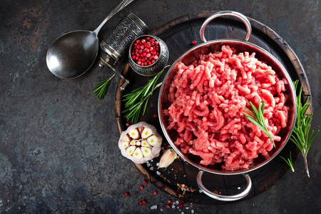 Cooking mince. Raw ground veal meat with ingredients for cooking on black kitchen table. Fresh minced meat, top view Foto de archivo