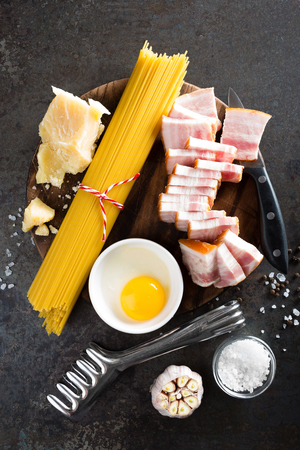 Ingredients for cooking Carbonara pasta, spaghetti with pancetta, egg and hard parmesan cheese. Traditional italian cuisine. Pasta alla carbonara