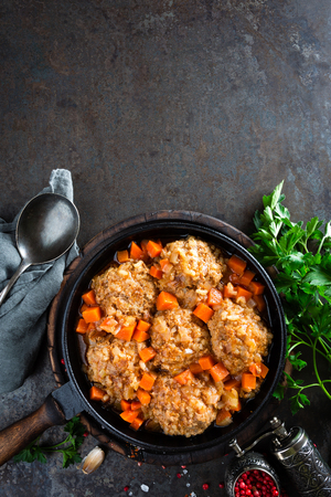 Veal meatballs stewed in frying pan with carrot in vegetable sauce. Delicious meat dish