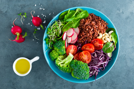Buddha bowl meal with kale, spinach and chard leaves, brown rice, tomato, broccoli, radish, fresh green sprouts and pine nuts. Healthy balanced nutrition. Vegetarian food. Overhead view