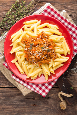 Pasta bolognese. Pasta served with a sauce of ground beef meat, tomato, onion, carrot and thyme. Traditional italian cuisine. Top view Фото со стока - 97128541