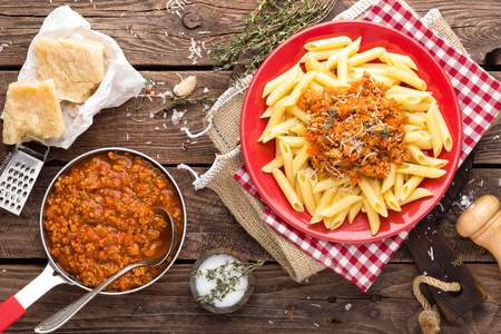 Pasta bolognese. Pasta served with a sauce of ground beef meat, tomato, onion, carrot and thyme. Traditional italian cuisine. Top view