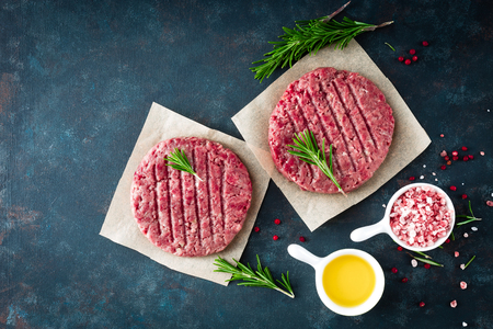 Fresh minced beef meat burgers with spices on dark background. Raw ground beef meat. Flat lay. Top view