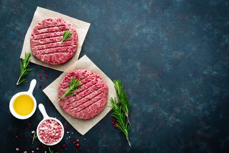 Hamburger tritati freschi della carne del manzo con le spezie su fondo scuro. Carne macinata di manzo cruda. Disteso. Vista dall'alto