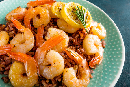Prawns roasted on grill and boiled brown rice on plate. Grilled shrimps, prawns with rice. Seafood. Asian cuisine. Closeup. Dark background