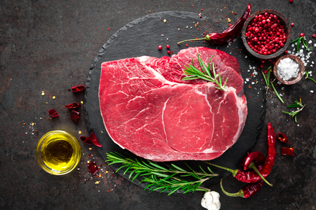Raw beef steak on black background with cooking ingredients. Fresh beef meat. Top view Фото со стока