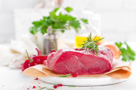 Raw beef meat tenderloin on white background with cooking ingredients closeup. Fresh beef meat on kitchen table Stock Photo