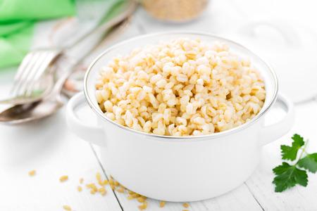 Bulgur wheat. Boiled bulgur cereal in pot on white kitchen table. Healthy vegetarian food