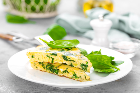 Omelet with spinach leaves. Omelette on plate, scrambled eggs Stockfoto