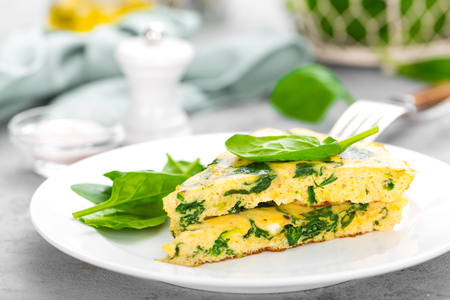 Omelet with spinach leaves. Omelette on plate, scrambled eggs 스톡 콘텐츠