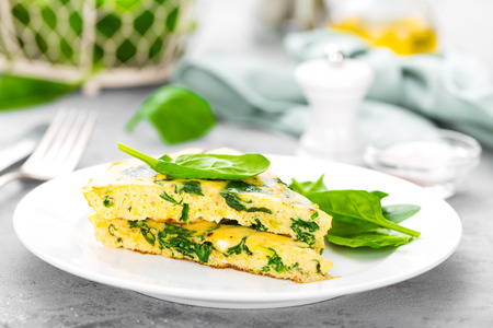 Omelet with spinach leaves. Omelette on plate, scrambled eggs Banco de Imagens - 98705520