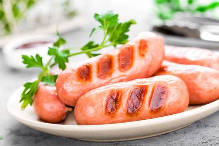 Grilled sausages on plate. BBQ sausages. Stock Photo