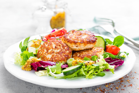 Cutlets and fresh vegetable salad on white plate. Fried meatballs with vegetable salad Foto de archivo - 99454403