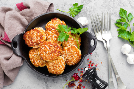 Cutlets. Fried cutlets in cast-iron pan on table Imagens