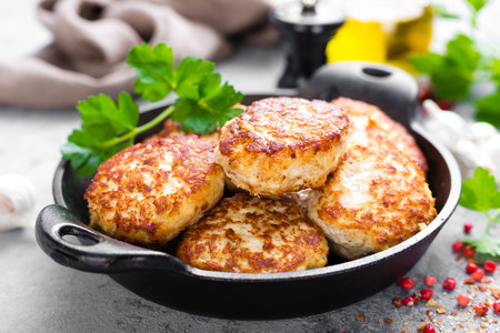 Cutlets. Fried cutlets in cast-iron pan on table Banco de Imagens