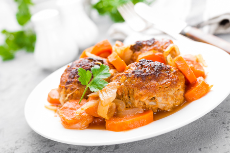 Fish meatballs or noisettes baked with carrot, onion and tomato sauce. Fish meatballs on plate