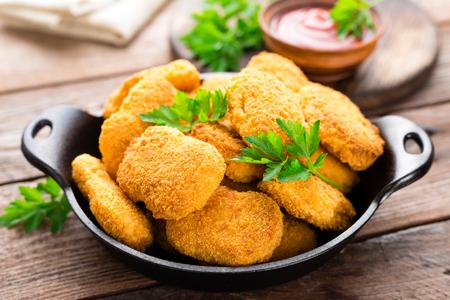 Nuggets. Kipnuggets met ketchup op houten tafel. Fast food