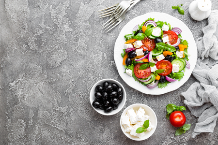 Greek salad. Fresh vegetable salad with tomato, onion, cucumbers, basil, pepper, olives, lettuce and feta cheese. Greek salad on plate Standard-Bild