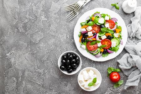Greek salad. Fresh vegetable salad with tomato, onion, cucumbers, basil, pepper, olives, lettuce and feta cheese. Greek salad on plate Standard-Bild