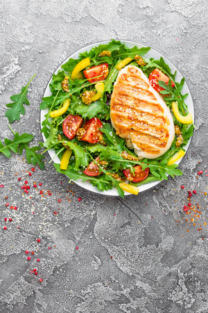 Chicken salad. Meat salad with fresh tomato, sweet pepper, arugula and grilled chicken breast. Chicken fillet with fresh vegetable salad Stock Photo