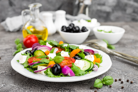 Greek salad. Fresh vegetable salad with tomato, onion, cucumbers, basil, pepper, olives, lettuce and feta cheese. Greek salad on plate Stock Photo