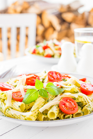 Pasta with basil pesto, tomato and cheese on plate Stock Photo
