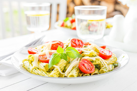 Pasta with basil pesto, tomato and cheese on plate Standard-Bild - 103953973